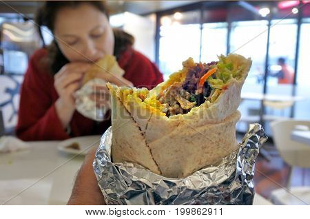 Close up of person eats Kebab wrap with grilled lamb and vegetables.