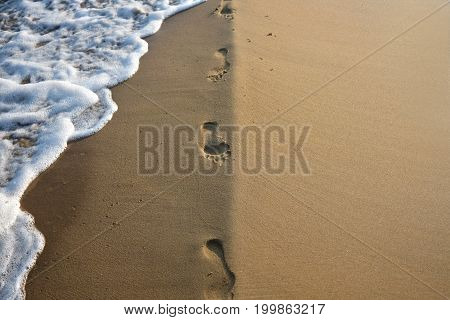 Footprints in the sand with sea wave and natural straight coast line with free copyspace
