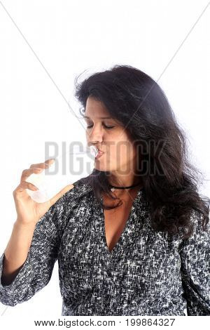 Latina Woman drinks water. A beautiful Hispanic Woman Enjoys a bottle of fresh cold water. isolated on white. room for text.