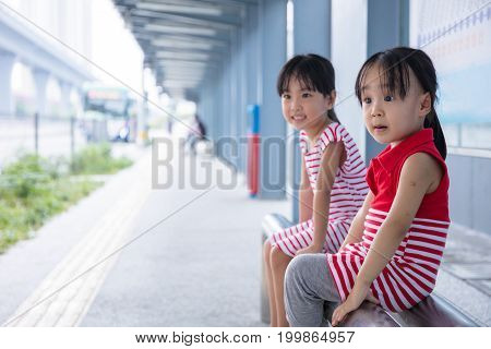 Asian Chinese little girls waiting for a bus at bus stop