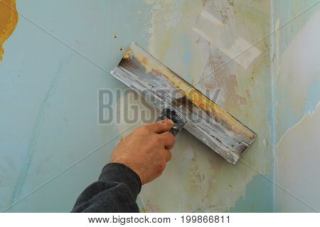 Man's Hand In A Gray Glove With Spatula In The Repair Room.