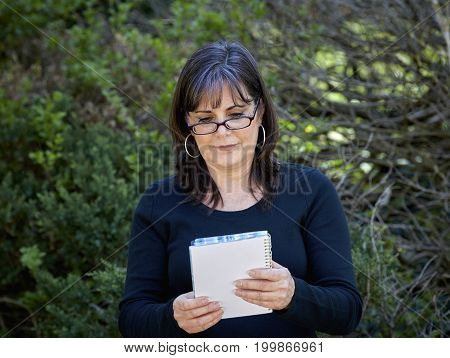 Middle Aged Woman Wearing Reading Glasses Looking At Notebook
