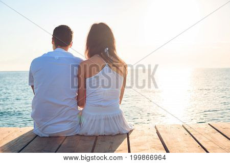 young couple by the sea with the sun rising in the background