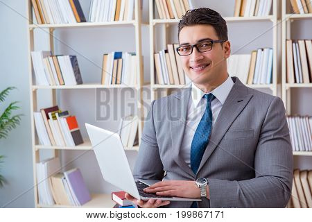 Businessman with a laptop working in the library