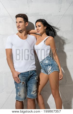 Sexy young couple posing together against white brick wall on sunny day