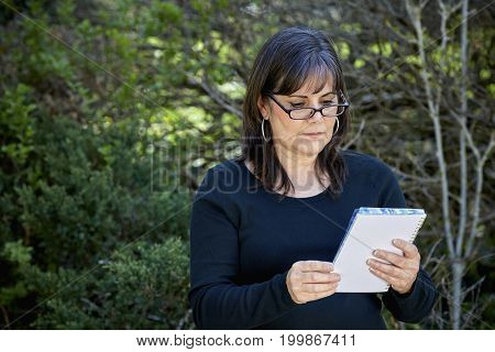 Middle Aged Woman Looking At Notebook