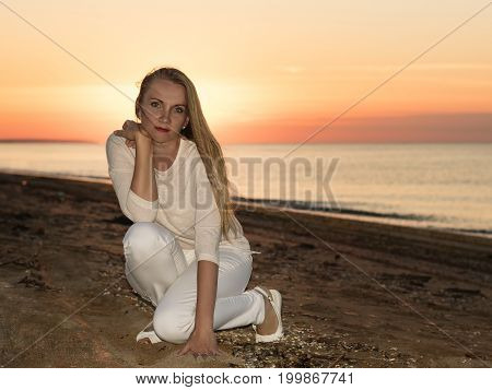 Woman in white dress on a sandy beach at sunset. Portrait of beautiful woman at sunset on the coast.