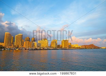 Honolulu cityscape in early morning before the rain Hawaii USA. Urban landscape of Honolulu from the water at sunrise.