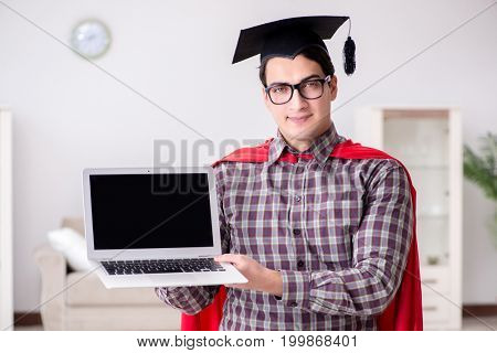 Super hero student wearing mortarboard and holding a laptop