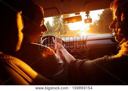 The couple drives the car on the way to the sunset. He drives the car she holds his hand. They go on an empty road and talk. Go to the sunset. Travel of lovers.