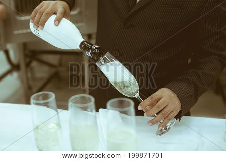 Waiter Pour Cocktail In Glass For Service In Luxury Dinner Party, Blurry Background With Vintage Col