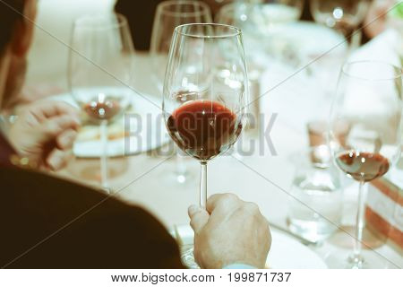 Blurry Background, Red Wine In Hand Of Man On The Table On Dinner Party In The Restaurant With Color