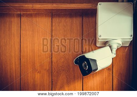 Security Camera Or Cctv Camera On Wooden Wall In The Room.