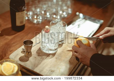 Bartender Cutting Peel Orange  On Chopping Wood And Counter Bar In Luxury Dinner Party, Blurry Backg
