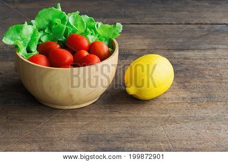 Fresh tomato and lettuce in wood bowl and lemon put on wood table.Side view of tomato and green oak lettuce with copy space for background.Fresh green oak lettuce tomato and lemon prepare for cooking. Fresh vegetable concept for background.
