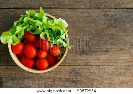 Fresh tomato and lettuce in wood bowl put on wood table. Top view or flat lay of tomato and green oak lettuce with copy space for background. Fresh green oak lettuce and tomato prepare for cooking. Fresh vegetable concept for background.