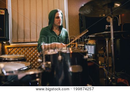 Drummer rehearsing on drums in recording studio. Music band playing before live concert