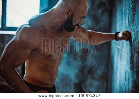 Young strong man fighter strike stone wall. Focus on face.