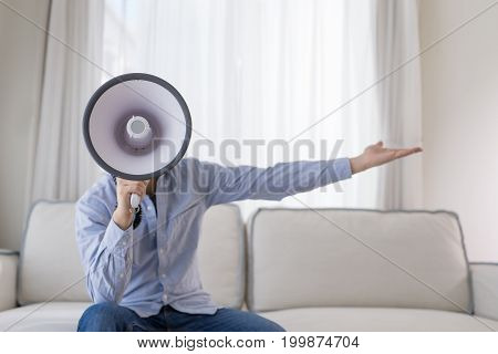 man take microphone and sit on sofa at home