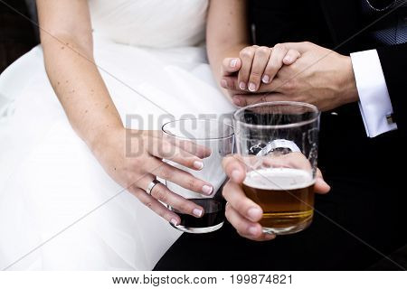 A bride and groom having a rest moment with drinks