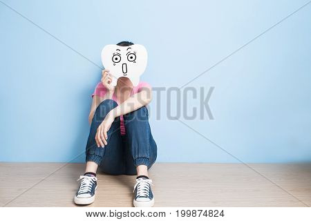 woman take surprise tooth on blue background