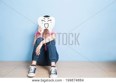 woman take smile tooth on blue background