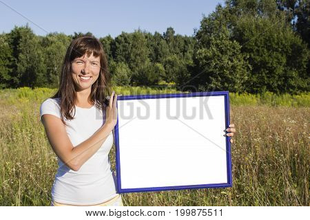girl standing in field of flowers holding an empty layout. mock up