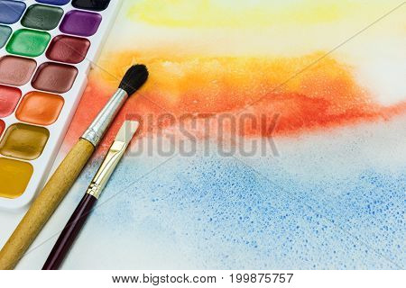 Paintbrushes And Palette Of Aquarelle Paints On Watercolor Background