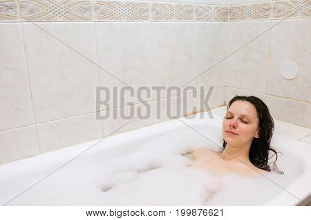 young beautiful girl in a bath with foam.