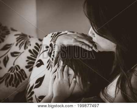 Black and white with grain of sad little boy being hugged by his mother at home. Parenthood Love and togetherness concept.