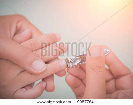 Family activity soft focus of mother hand cut nails for kid by using nail clipper.