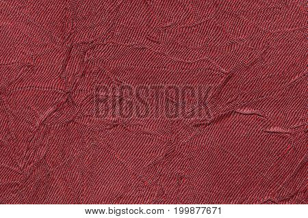Dark red wavy background from a textile material. Fabric with fold texture closeup. Creased shiny maroon cloth.