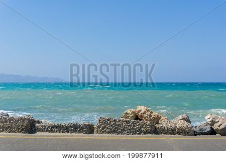 View on a beautiful turquoise Ocean in front of a blue Sky. Close-up  of a Stones in front of a turquoise Sea in Summer.