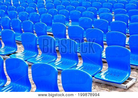 Lot of empty blue plastic seats in a row