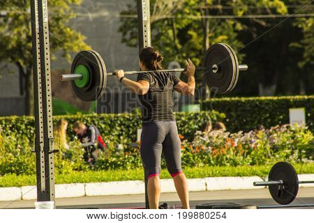 A woman is holding a barbell on her shoulders. Exercise on the street.
