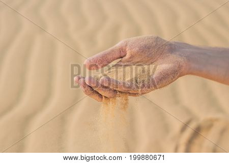 Desert, Sand Puffs Through The Fingers Of A Man's Hand
