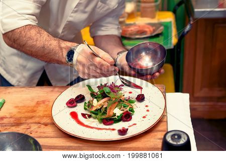 Professional chef is pouring red sauce on vegetable and berry appetizer, toned image