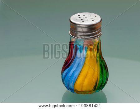 Salt shaker made of coloured glass standing on glass