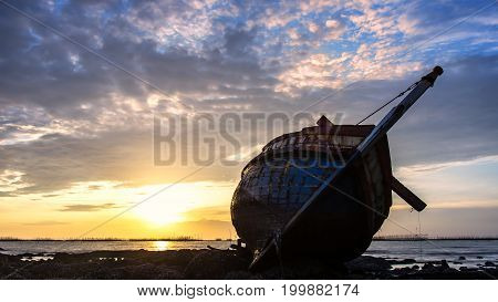 Boat deteriorate breaking down laying in the coast side with sunset in background