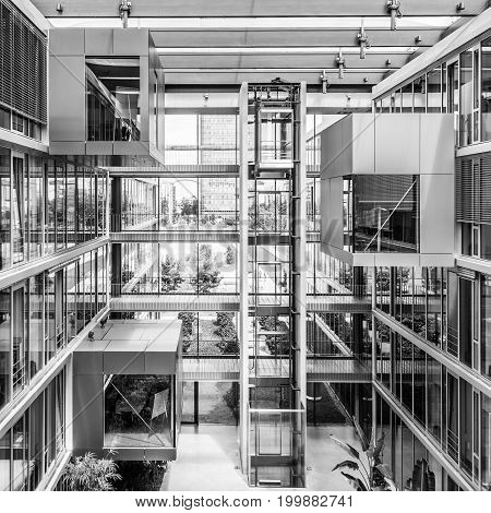 Main hall, staircase and windows of morden office building. Contemporary corporate business architecture. Munich Trading and Technology Centre. Black and white image.