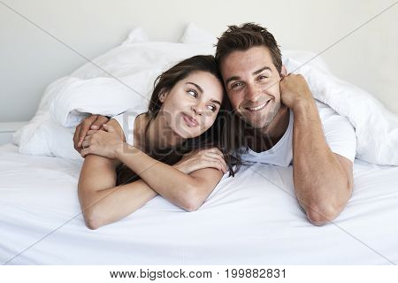 Good looking couple lying in bed portrait