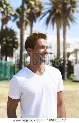 Smiling guy in white t-shirt looking away