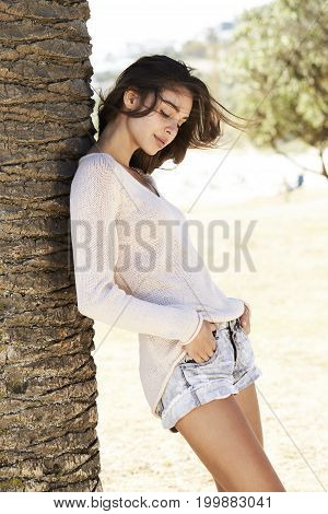 Young Brunette beach babe leaning against tree