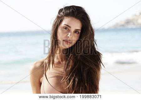 Young Beach brunette babe looking at camera
