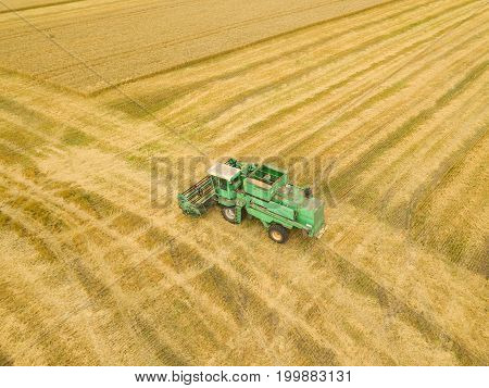 Top view combine harvester gathers the wheat at sunset. Harvesting grain field crop season. Beautiful natural aerial landscape