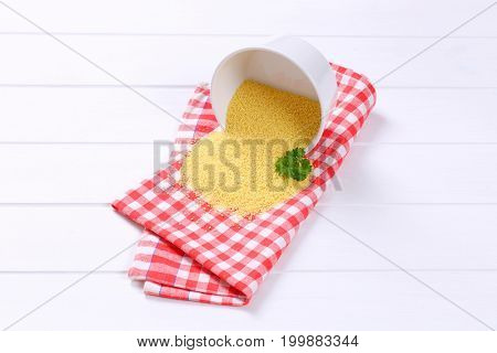 bowl of raw couscous split out on checkered place mat