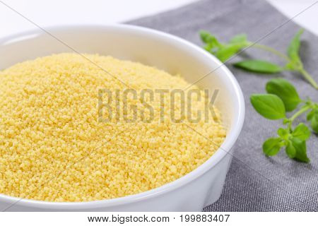 bowl of raw couscous on grey place mat - close up