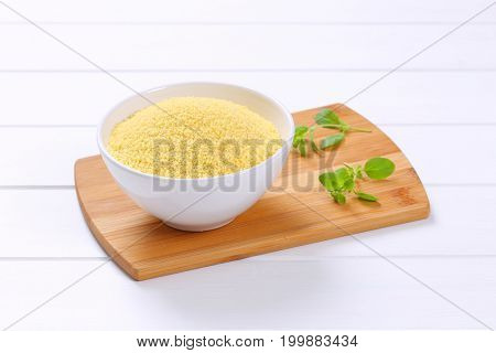 bowl of raw couscous on wooden cutting board