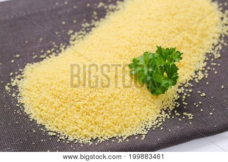 pile of raw couscous on grey place mat - close up