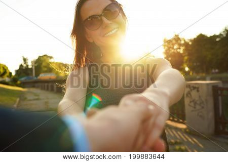Follow me - happy young woman pulling guy's hand - hand in hand walking on a bright sunny day - concept of carefree modern life